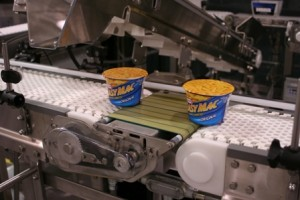 powered transfer display transfer of instance Mac and cheese cups across conveyor belts